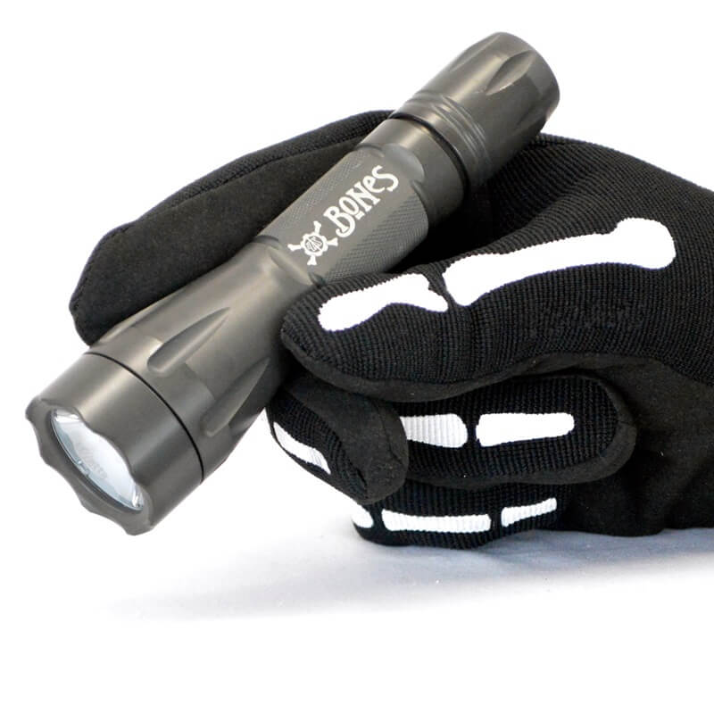 Elzetta Bones Flashlight in gloved hand (obsolete logo shown)